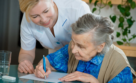 caregiver assisted the elderly woman in writing