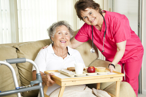 portrait of a smiling caregiver and elderly woman while holding her meal