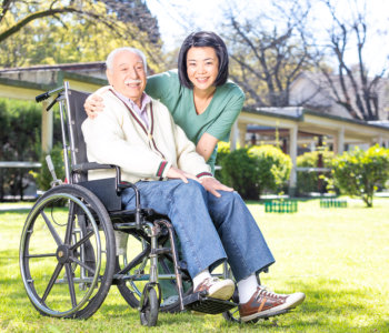 a nurse helping elder man on wheelchair at rehab facility garden